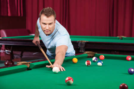 pool table: Man playing pool. Confident young man playing pool and looking ahead Stock Photo
