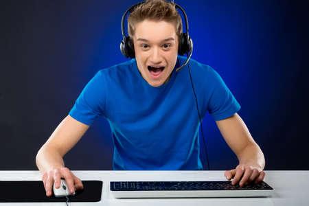 jugando videojuegos: Emocionado gamer. Adolescente emocionado que juega juegos de video en su computadora Foto de archivo