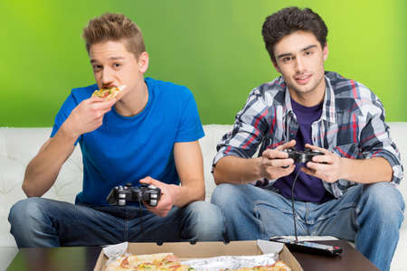 Two young gamers playing video games while sitting on the couch photo