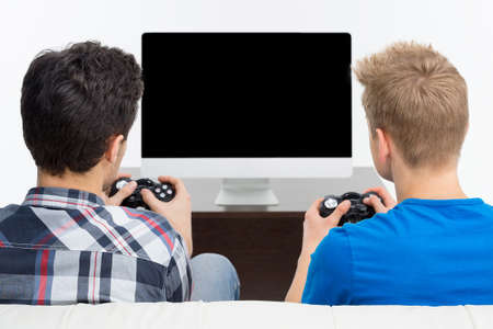 video game: Rear view of two young gamers playing video games