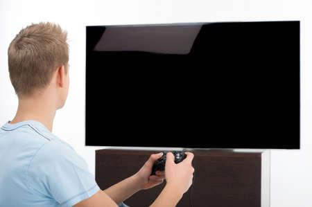 jugando videojuegos: Gamer con joystick. Vista posterior del joven jugador jugando juegos de video Foto de archivo