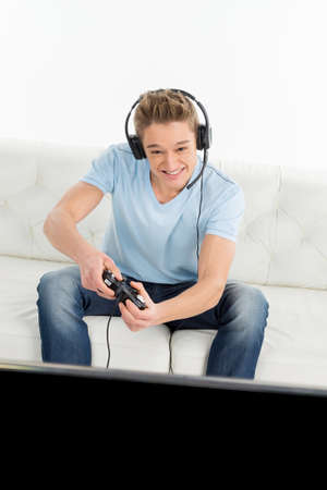 Gamerswith joystick. Young gamers playing video games while sitting on the couch photo