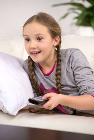 pigtails: Cute girl at home. Cheerful little girl watching TV and smiling