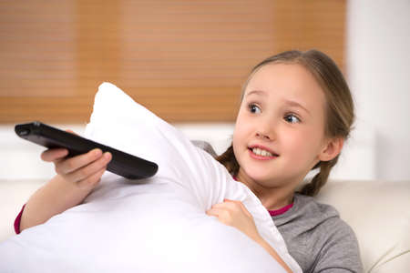 pigtails: Scared little girl. Cute little girl holding remote control and looking scared Stock Photo