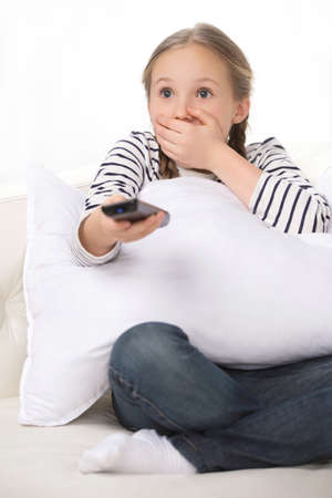 Shocked little girl. Little girl holding remote control and looking scared photo