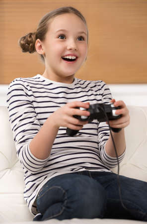 Girl with joystick. Excited little girl playing video game and smiling photo
