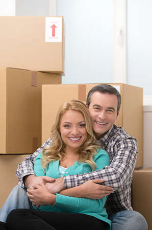 House moving. Beautiful middle-aged couple sitting together near the cardboard boxes and smiling photo