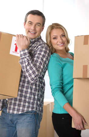 House moving. Beautiful middle-aged couple standing close to each other and holding cardboard boxes photo