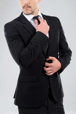 handcarves: Bossy men. Bossy young men adjusting his necktie while standing isolated on grey