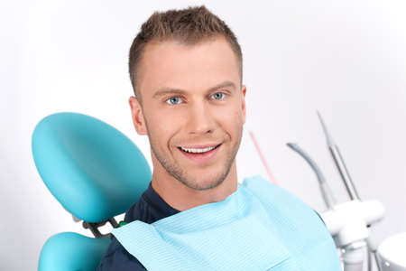 man in chair: Patient at dentist office. Cheerful young man sitting at the chair in dental office and smiling