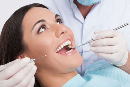 dentist woman: Patient at dentist office. Close-up of young woman sitting at the chair in dental office and doctor examining teeth