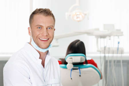 Cheerful dentist. Smiling young dentist looking at camera while patent sitting at the chair photo