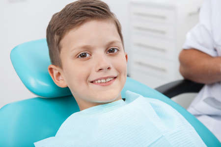 Patient at dentist office. Cheerful little boy sitting at the chair in dental office and smiling photo