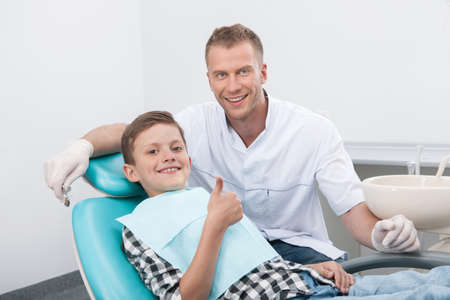 Patient at dentist office. Dentist and little patient looking at camera and smiling photo