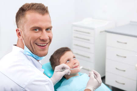 Little patient at dentist office. Little boy sitting at the chair at the dental office while doctor looking at camera and smiling photo