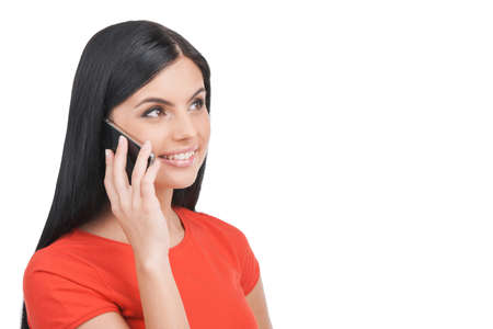 take away: Woman on the phone. Cheerful young woman talking on the mobile phone and smiling while standing isolated on white Stock Photo