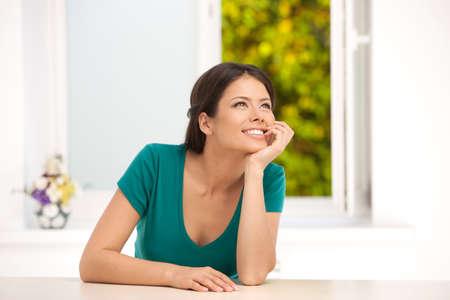 young woman sitting: Girl dreaming  Beautiful young woman sitting at the table and holding hand on chin Stock Photo