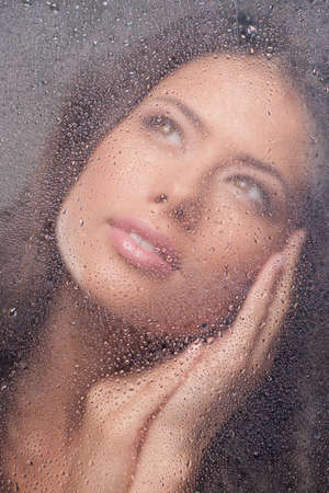 Girl dreaming. Beautiful young woman looking through wet window and smiling photo