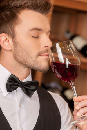 Confident sommelier. Side view of confident young sommelier holding a wine glass and keeping his eyes closed photo