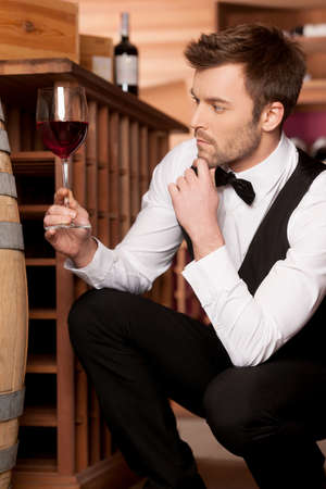 Confident sommelier  Thoughtful young sommelier holding a glass of wine while sitting near wine barrel Stock Photo