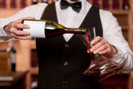 デカンター デカンターにワインを注ぐソムリエ トリミング像とソムリエ 写真素材