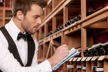 shop skill: Confident sommelier  Side view of confident young sommelier writing something at his note pad and looking at the wine bottles Stock Photo