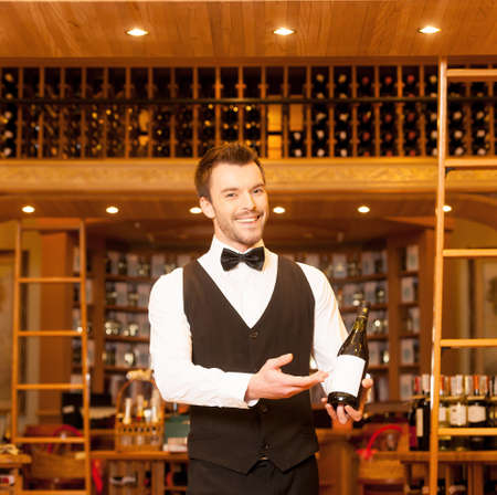 Confident sommelier  Cheerful young sommelier holding a wine bottle and pointing it photo