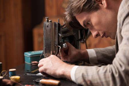 Tailor bei der Arbeit. Selbstbewusste junge Schneider arbeitet an der Schneiderei Standard-Bild