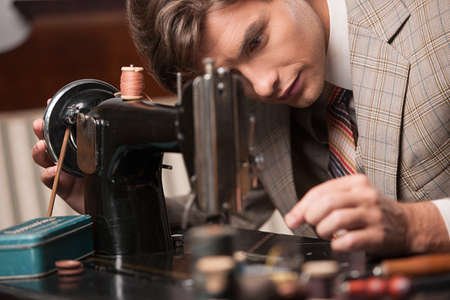 tailor suit: Tailor at work. Confident young tailor sewing clothes at the tailor shop