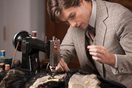 tailor measure: Young tailor at work. Confident young tailor sewing clothes at the tailor shop Stock Photo