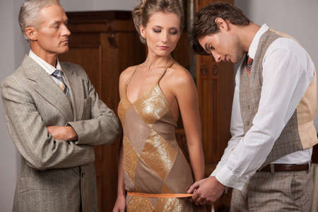 tailor measure: Tailor at work. Confident young tailor measuring young woman with measuring tape while man in formalwear standing near them