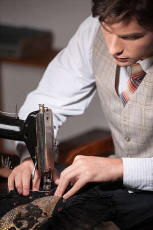 tailor measure: Young tailor at work. Confident young tailor working at the tailor shop Stock Photo