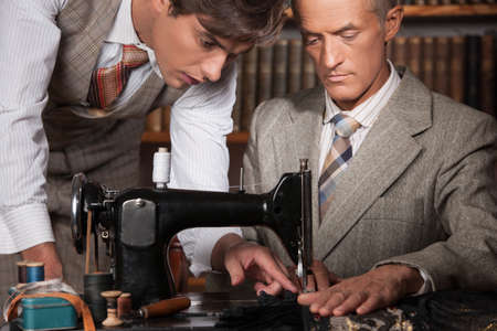 tailor measure: Tailors at work. Two confident tailors working at tailor shop