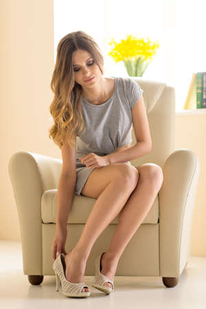 undressing woman: Beauty at home. Beautiful young woman in dress wearing shoes