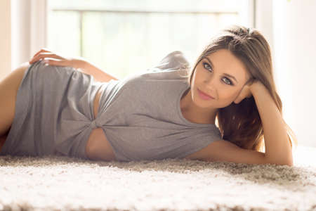 lying on side: Day off at home. Attractive young woman in dress lying on the carpet and smiling