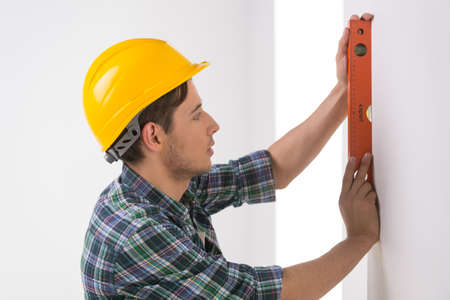 Handyman measuring wall. Confident craftsperson in hardhat measuring the wall level Stock Photo - 22456886