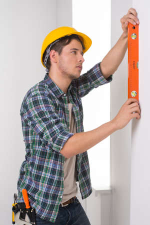 Handyman. Confident craftsperson in hardhat measuring the wall level Stock Photo - 22456889