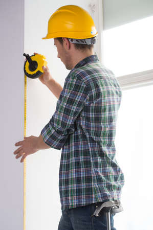 Handyman. Rear view of confident craftsperson in hardhat measuring the wall level Stock Photo - 22456894