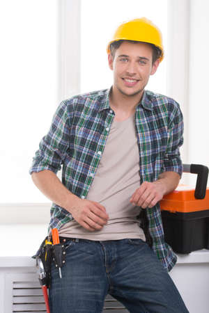 class maintenance: Handyman. Cheerful craftsperson looking at camera and leaning at the windowsill
