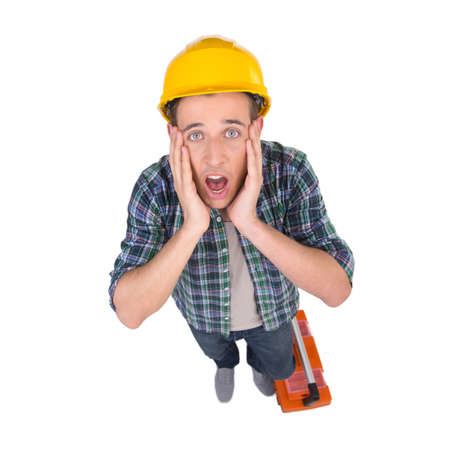 Handyman. Top view of frustrated craftsperson looking at camera and holding head in hands while isolated on white photo