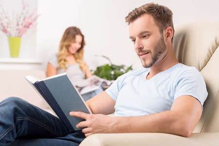 woman reading book: Couple at home. Cheerful young man reading book while his girlfriend sitting and smiling
