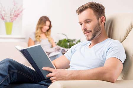 mujer leyendo libro: Pareja en el hogar. Alegre joven leyendo libro mientras su novia sentado y sonriente Foto de archivo