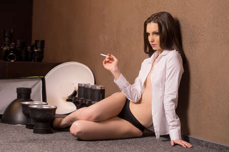 women smoking: Model at studio. Beautiful young fashion model sitting at photo studio and smoking