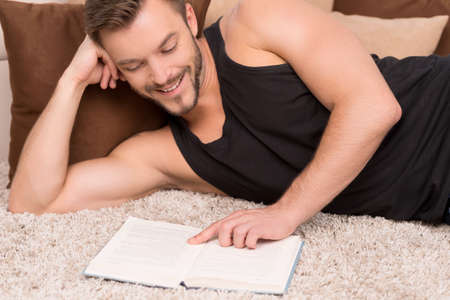 lying on side: Relaxing at home. Cheerful young man lying on the carpet and reading book