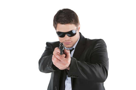 man holding gun: Bodyguard. Confident young man holding gun and aiming camera while standing isolated on white Stock Photo
