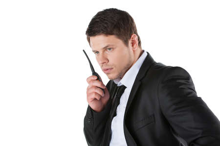 police radio: Bodyguard. Confident young man in formalwear talking on radio set while standing isolated on white Stock Photo