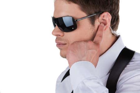 agent de sécurité: Bodyguard. Grave jeune homme en lunettes de soleil et un casque debout isolé sur blanc Banque d'images