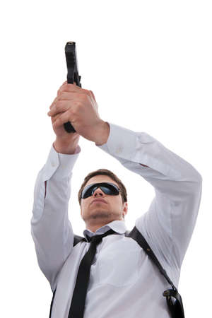 Bodyguard. Low angle view of serious young man in sunglasses holding gun while standing isolated on white photo