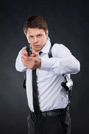 man holding gun: Bodyguard. Confident young man in shirt and tie holding gun and aiming you while standing against black background
