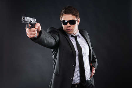 man holding gun: Bodyguard. Confident young man in formalwear holding gun and aiming somewhere while standing against black background Stock Photo